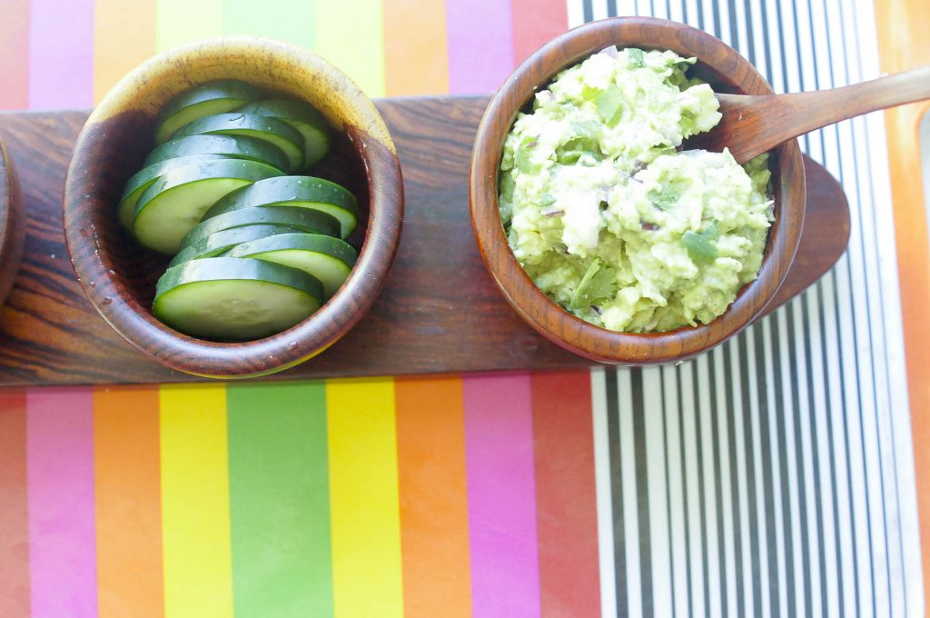 Guacamole in bowl next to cucumbers